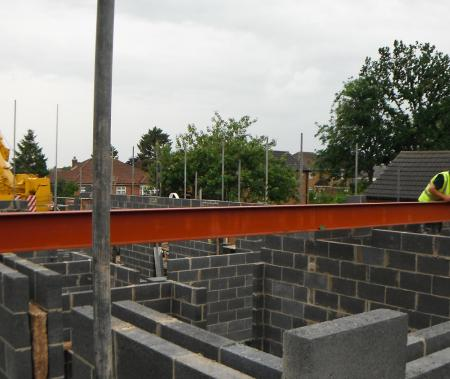 Steel girders being swung into place to form part of the major structure of the open plan living space