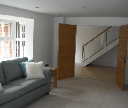 Lounge with double doors opening into spacious hallway
