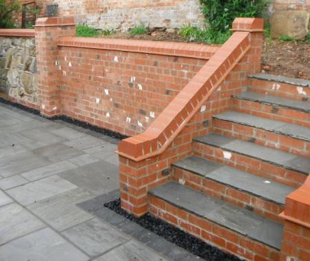 New brick staircase provides easy access to reconstructed raised bed and retaining wall